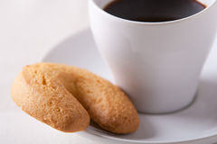 Taza de café del café express con una galleta en el platillo Foto de archivo libre de regalías