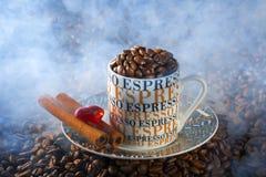 Taza de café del café express en un ambiente de granos de café fritos Imagen de archivo libre de regalías