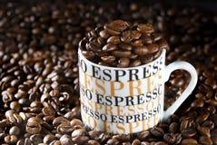 Taza de café del café express en un ambiente de granos de café fritos Imagenes de archivo