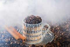 Taza de café del café express en un ambiente de granos de café fritos Foto de archivo