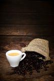 Taza de café del café express y granos de café imagenes de archivo