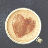 Taza de café del capuchino con espuma bajo la forma de corazón en azul Imagenes de archivo
