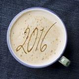 Taza de café del capuchino en el dril de algodón azul, fondo de los vaqueros Fecha 2 Imagen de archivo