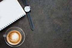 Taza de café del latte, de cuaderno y de reloj en fondo negro Fotografía de archivo