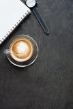 Taza de café del latte, de cuaderno y de reloj en fondo negro Fotos de archivo libres de regalías