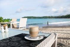 Taza de café del Latte por la playa fotografía de archivo