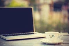 Taza de café del latte y laptob calientes en cafetería - efecto del vintage Foto de archivo libre de regalías