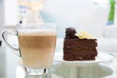 Taza de café del Latte y torta de chocolate en fondo Imagen de archivo