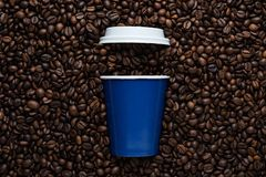 Taza de café disponible azul a ir con una tapa blanca en el fondo de habas asadas imagen de archivo libre de regalías