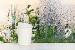 Taza de café disponible blanca en una tabla que acerca al fondo de la ventana del día lluvioso Imágenes de archivo libres de regalías