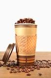 Taza de café disponible con las habas fotos de archivo