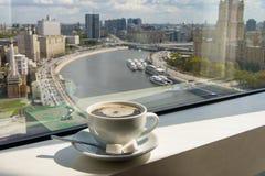 Taza de café en alféizar con la opinión de la ciudad Foto de archivo libre de regalías