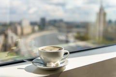 Taza de café en alféizar con la opinión de la ciudad Imagenes de archivo