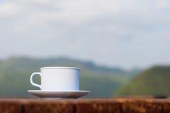 Taza de café en de madera y la montaña (fondo del vintage) Imágenes de archivo libres de regalías