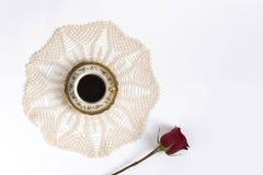 Taza de café en el centro de un cordón con una rosa roja Imágenes de archivo libres de regalías