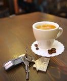 Taza de café en el escritorio y las llaves Foto de archivo libre de regalías