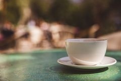 Taza de café en el fondo al aire libre de la tabla de verde menta - imágenes suaves del estilo del efecto luminoso fotos de archivo