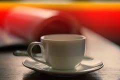 Taza de café en el fondo de una revista abierta Fotos de archivo libres de regalías