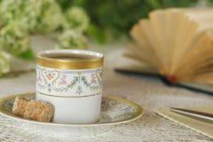 Taza de café en el jardín con un libro, una pluma y un papel abiertos Imagen de archivo