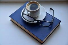 Taza de café en el libro de lectura con los vidrios Imagen de archivo