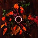Taza de café en el medio de las flores y de las herraduras Foto de archivo libre de regalías