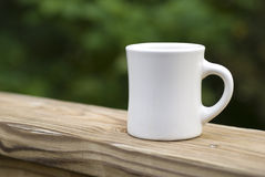 Taza de café en el pasamano Imagen de archivo libre de regalías