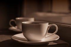 Taza de café en el travesaño de la ventana Fotos de archivo libres de regalías