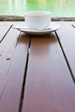 Taza de café en el vector de madera Foto de archivo libre de regalías