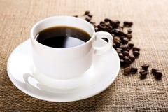 Taza de café en fondo de la arpillera Foto de archivo libre de regalías
