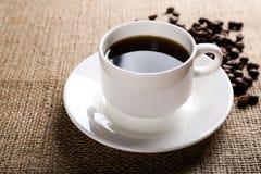 Taza de café en fondo de la arpillera Imágenes de archivo libres de regalías