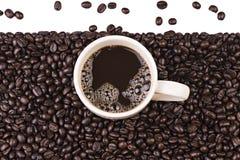 Taza de café en fondo de los granos de café Fotos de archivo libres de regalías