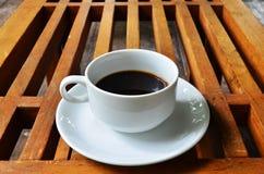 Taza de café en fondo de madera de la tabla foto de archivo