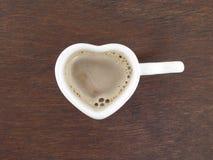 Taza de café en forma de corazón en piso de madera Imagenes de archivo