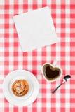 Taza de café en forma de corazón y un bollo de canela Fotos de archivo