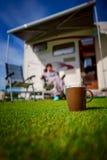 Taza de café en hierba Viaje de las vacaciones de familia, viaje del día de fiesta en mot Foto de archivo libre de regalías
