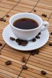 Taza de café en la estera de bambú Fotos de archivo
