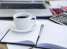 Taza de café en la oficina sobre los papeles financieros y orden del día Café Bre fotografía de archivo libre de regalías