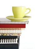 Taza de café en la pila de cuaderno Fotos de archivo libres de regalías