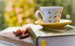 Taza de café en la placa de madera del grunge del libro, backgroun verde de la hoja Imagen de archivo libre de regalías