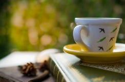 Taza de café en la placa de madera del grunge del libro, fondo verde de la hoja Foto de archivo