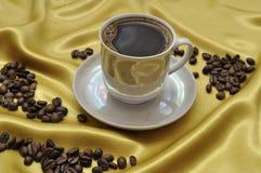 Taza de café en la seda de oro Fotos de archivo libres de regalías