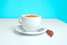 Taza de café en la tabla con las habas Fotografía de archivo libre de regalías
