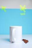 Taza de café en la tabla con las habas Foto de archivo libre de regalías