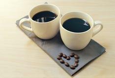 Taza de café en la tabla de madera con la forma del corazón hecha de haba Foto de archivo libre de regalías