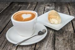 Taza de café en la tabla de madera con la panadería en fondo Imagen de archivo