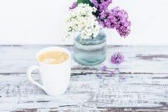 Taza de café en la tabla de madera del vintage con con las ramas de la lila en florero de cristal transparente Fotos de archivo