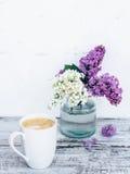 Taza de café en la tabla de madera del vintage con con las ramas de la lila en florero de cristal transparente Imágenes de archivo libres de regalías