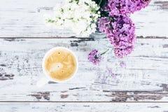 Taza de café en la tabla de madera del vintage con con las ramas de la lila en florero de cristal transparente Imagen de archivo libre de regalías