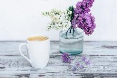 Taza de café en la tabla de madera del vintage con con las ramas de la lila en florero de cristal transparente Imagen de archivo