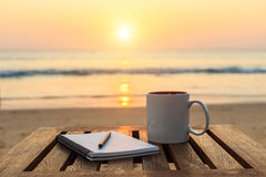 taza de café en la tabla de madera en la puesta del sol o la playa de la salida del sol imágenes de archivo libres de regalías